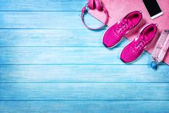 Set for sports activities on blue wooden background, top view. Fitness shoes over blue planks background. Sport shoes and accessories for sports activities on stock photos