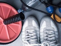 Set for sports activities on grey background. Healthy lifestyle concept. Sport equipment sport shoes, hand expander, wheel press. Roll and bottle of water stock images