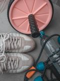 Set for sports activities on grey background. Healthy lifestyle concept. Sport equipment sport shoes, hand expander, wheel press. Roll and bottle of water stock photography