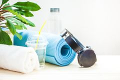 Set for sports. Blue yoga mat towel headphones and a bottle of water on a light background The concept of a healthy lifestyle Copy royalty free stock photos