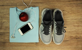 Set for sports: shoes, t-shirt, mobile phone with headphones and red apple close-up on a wooden background, top view Stock Photos