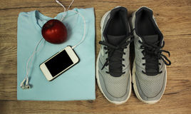 Set for sports: shoes, t-shirt, mobile phone with headphones and red apple close-up on a wooden background, top view Royalty Free Stock Photos