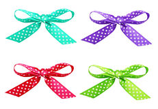 Set of spotted ribbon bows. Set of red, purple, blue and green spotted ribbon bows isolated on white Royalty Free Stock Photos