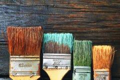 Set stary muśnięcie dla barwić ściany na drewnianym tle Fotografia Royalty Free