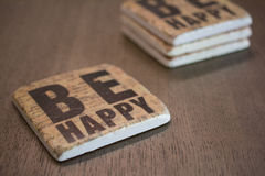 A set of stone coasters stacked on a wooden table surface reading Be Happy Royalty Free Stock Photos