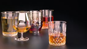 A set of strong alcoholic beverages in glasses, in the presence of whiskey, vodka, rum, brandy, tequila, on a dark background stock images