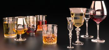 A set of strong alcoholic beverages in glasses, in the presence of whiskey, vodka, rum, brandy, tequila, on a dark background royalty free stock photo