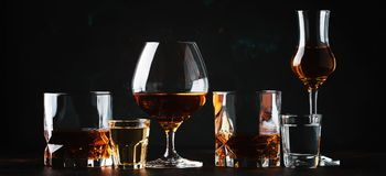 Set of strong alcoholic drinks in glasses and shot glass in assortent: vodka, rum, cognac, tequila, brandy and whiskey. Dark. Vintage background, selective stock photo