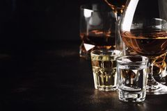 Set of strong alcoholic drinks in glasses and shot glass in assortent: vodka, rum, cognac, tequila, brandy and whiskey. Dark. Vintage background, selective stock photography