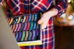 Set stubarwne pastelowe kredki w otwartym artysty pudełku w kobiet rękach Artysty obraz na sztaludze zdjęcie stock