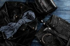 Set of stylish black women`s clothing, women`s fashion accessories, black style, on blue wooden background. flat lay,. Top view royalty free stock photography