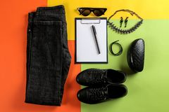 Set of stylish black women`s clothing, fashionable women`s accessories on a colorful background. flat lay royalty free stock photo