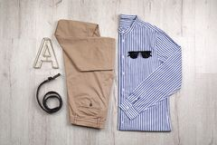 Set of stylish clothes and accessories on wooden floor. Flat lay Stock Images