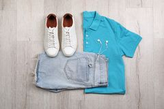 Set of stylish clothes and accessories on wooden floor. Flat lay Stock Photos