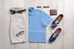 Set of stylish clothes and accessories on wooden floor, flat lay. Composition Stock Image