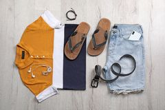 Set of stylish clothes and accessories on wooden floor. Flat lay Royalty Free Stock Photo