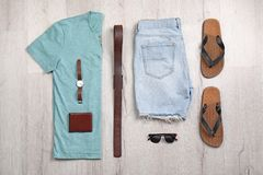 Set of stylish clothes and accessories on wooden floor. Flat lay Stock Photography