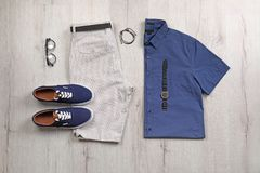Set of stylish clothes and accessories on wooden floor. Flat lay Stock Photo