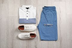 Set of stylish clothes and accessories on wooden floor. Flat lay Royalty Free Stock Images