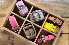 Set of stylish vintage belts in wooden crate royalty free stock photos