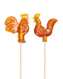 Set of sugar lollipop made in the shape of cockerels on a wooden stick. Isolated on the white Stock Photos