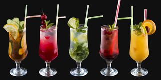 A set of summer cold drinks in glasses. On a black background royalty free stock photos