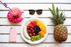Set of summer. Fresh fruit plate and pineapple, top view from above. Phone and drink Royalty Free Stock Photo