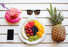 Set of summer. Fresh fruit plate and pineapple, top view from above. Phone and drink Stock Photo