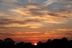 An Almost Set Sun in Cloudy Skies Royalty Free Stock Photo