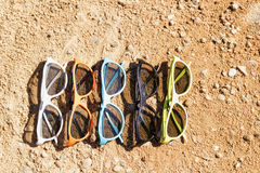 Set of sunglasses on the sand. Concept for sumer, vacation post Royalty Free Stock Photos