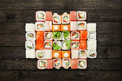 Set of sushi maki and rolls at black rustic wood. Royalty Free Stock Photos