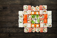 Set of sushi maki and rolls at black rustic wood. Royalty Free Stock Photography