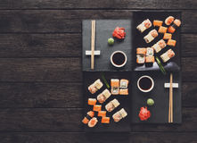 Set of sushi maki and rolls at black rustic wood. Stock Photography