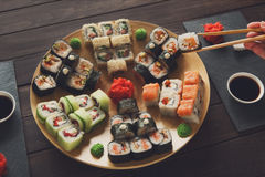 Set of sushi maki and rolls at black rustic wood. Royalty Free Stock Image