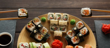 Set of sushi maki and rolls at black rustic wood. Royalty Free Stock Images