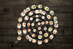 Set of sushi maki and rolls at black rustic wood. Stock Photos