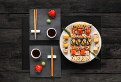Set of sushi maki and rolls on black rustic wood, top view. Japanese food restaurant, sushi maki gunkan roll platter. Set for two with chopsticks, ginger, soy Royalty Free Stock Photo