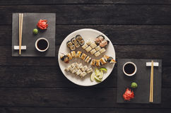 Set of sushi maki and rolls on black rustic wood, top view. Japanese food restaurant, unagi roll sushi and maki platter. Set for two with chopsticks, ginger, soy royalty free stock images