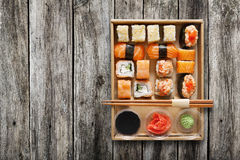 Set of sushi maki and rolls at box on wood. Royalty Free Stock Photos
