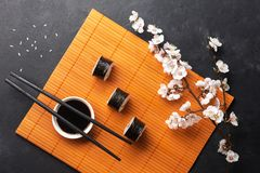 Set of sushi and maki rolls with branch of white flowers on stone table. Top view royalty free stock images