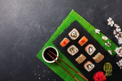 Set of sushi and maki rolls with branch of white flowers on stone table. Top view stock image