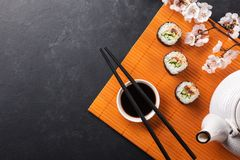 Set of sushi and maki rolls with branch of white flowers on stone table. Top view stock photo