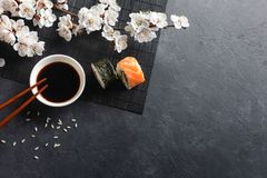 Set of sushi and maki rolls with branch of white flowers on stone table. Top view stock photography