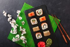 Set of sushi and maki rolls with branch of white flowers on stone table. Top view royalty free stock photo