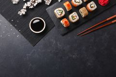 Set of sushi and maki rolls with branch of white flowers on stone table. Top view royalty free stock photography