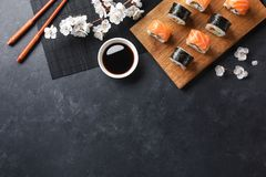 Set of sushi and maki rolls with branch of white flowers on stone table. Top view royalty free stock photos