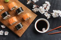 Set of sushi and maki rolls with branch of white flowers on stone table. Top view stock photos
