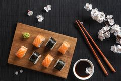 Set of sushi and maki rolls with branch of white flowers on stone table stock photos
