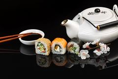 Set of sushi and maki rolls with white teapot with the inscription green tea on the glass table royalty free stock photography