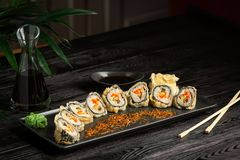 set of sushi rolls on a black plate on a black wooden background with green leaves of a houseplant royalty free stock photo